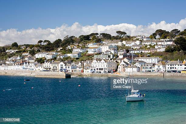 a yacht floating on the clear blue water in the small seaside harbour and coastal town of st mawes. - cornwall england stock pictures, royalty-free photos & images