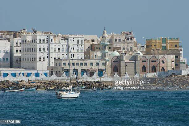Yacht in Gulf of Aden with mosque and buildings of Old Town in background.