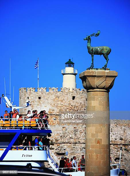 A yacht in the Mandraki Harbour with passengers passing the monument deer statue July 16 2009 in Rhodes Greece Rhodes is the largest of the Greek...