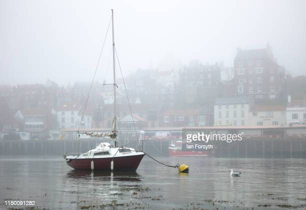 A yacht is moored at low tide as sea fog shrouds Whitby Harbour on May 18 2019 in Whitby England Heavy fog and mist covered many parts of the North...