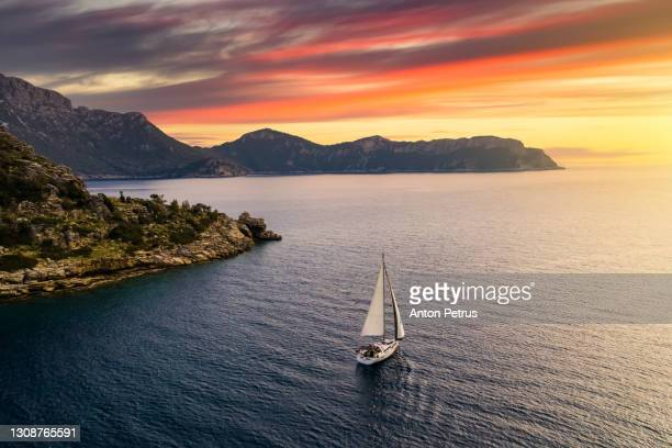 yacht near the rocky coast in turkey at sunset. yachting, luxury vacation at sea - wealth stock pictures, royalty-free photos & images