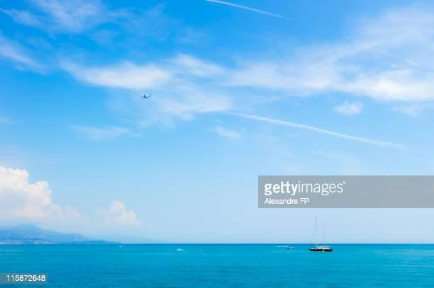 Yacht off Antibes shore and plane in sky