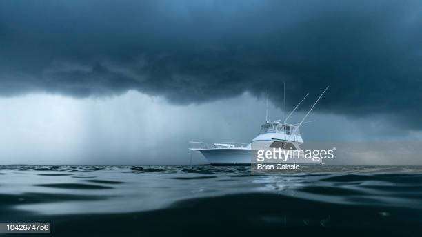 yacht on ominous stormy ocean - recreational boat stock pictures, royalty-free photos & images