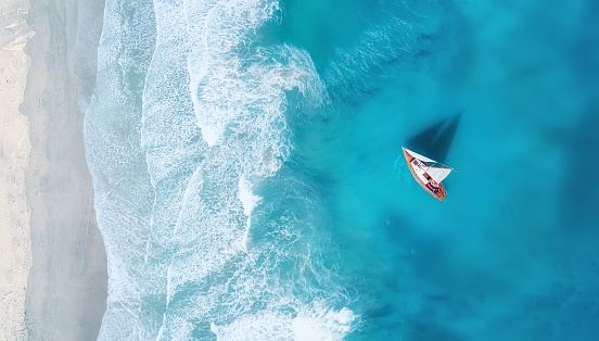 Yacht on the water surface from top view. Turquoise water background from top view. Summer seascape from air. Travel concept and idea 1066331604