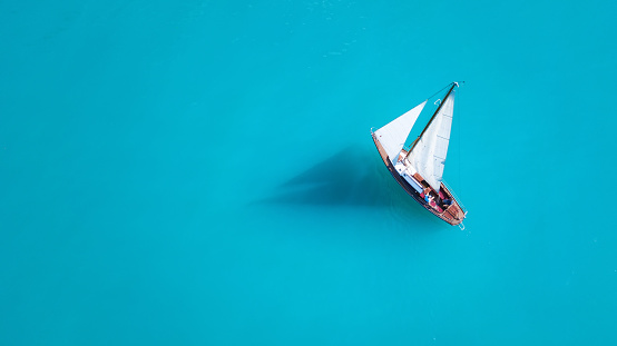 Yacht on the water surface from top view. Turquoise water background from top view. Summer seascape from air. Travel concept and idea 1068955204