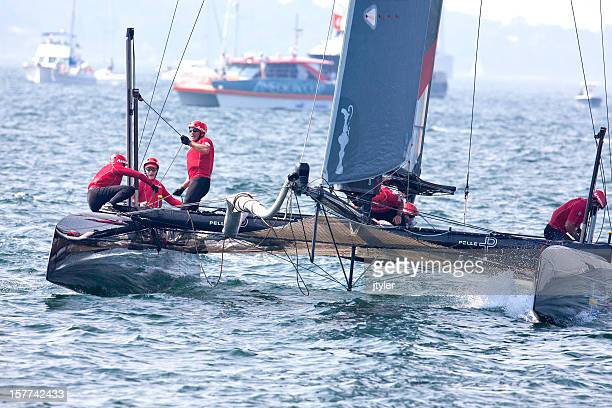 yacht racing crew hard at work - catamaran stock photos and pictures