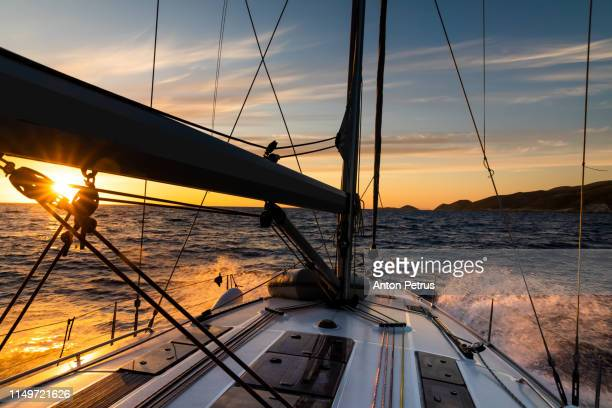 yacht sailing at sunset during a storm. luxury vacation at sea - 帆 ストックフォトと画像