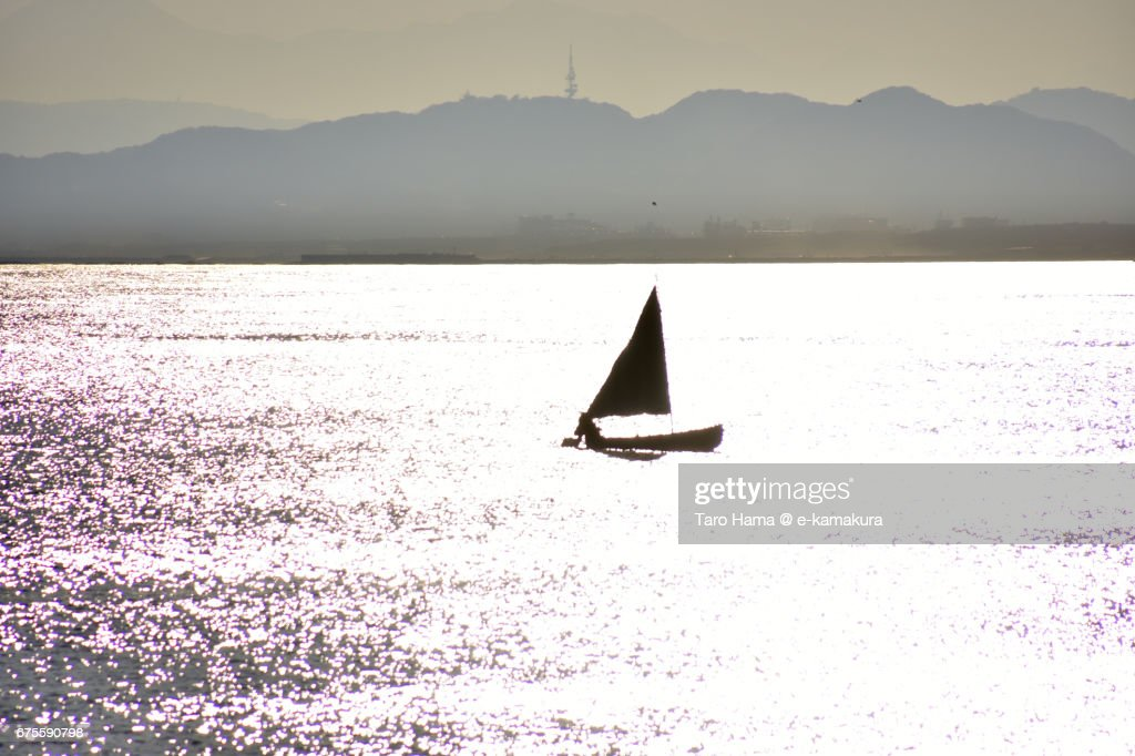 A yacht sailing on the sunset beach : ストックフォト