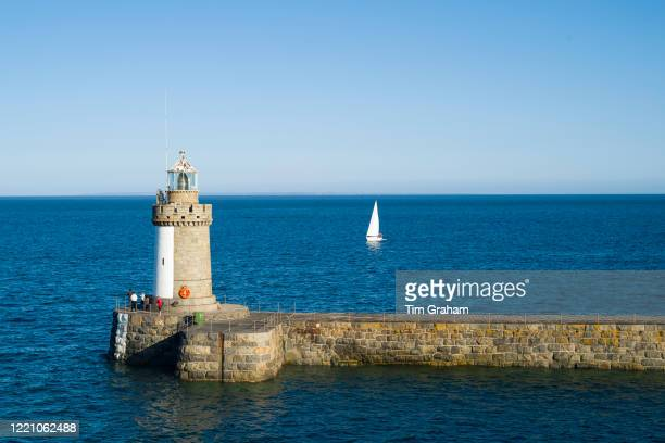 Yacht sailing past Guernsey island lighthouse and breakwater pier St Peter Port Channel Isles