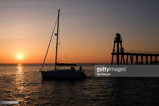 A yacht sails out of Whitby Harbour as the sun rises on Easter Sunday on April 21 2019 in Whitby United KingdomThis Easter weekend has broken...