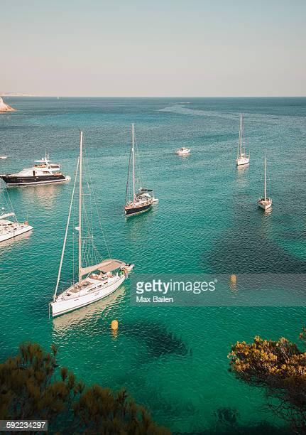 yachts anchored in bay at cala macarella, menorca, spain - カラマカレラ ストックフォトと画像