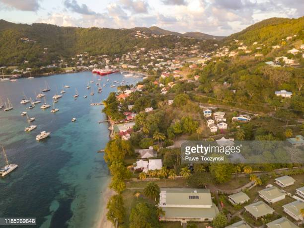 yachts and sail boats moored in the port elizabeth harbor bequia at sunset, saint vincent and the grenadines, 2019 - image stock pictures, royalty-free photos & images