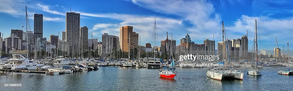 Yachts At Commercial Dock With City In Background : Stock Photo