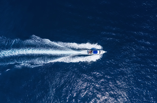 Yachts at the sea in Bali, Indonesia. Aerial view of luxury floating boat on transparent turquoise water at sunny day. Summer seascape from air. Top view from drone. Seascape with motorboat in bay. Travel - image 1144159632