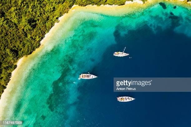 yachts in the bay near the green island. summer vacation, greece, kefalonia - peninsula de grecia fotografías e imágenes de stock