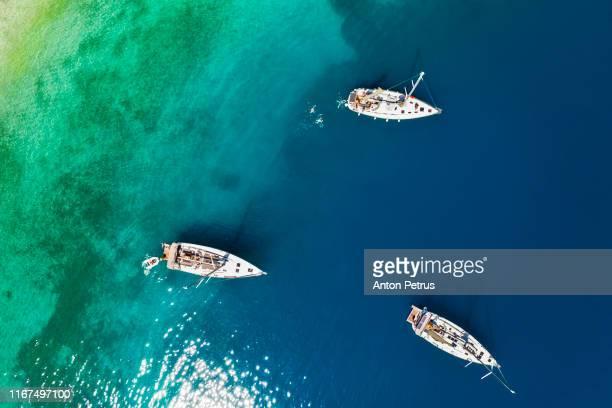 yachts in the bay near the green island. summer vacation, greece, mykonos - peninsula de grecia fotografías e imágenes de stock