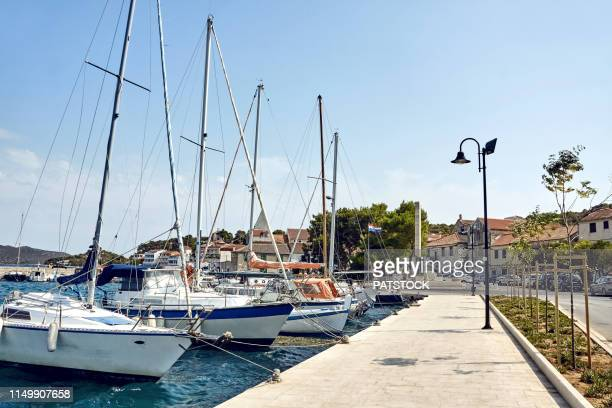 yachts moored by the strait dividing mainland and murter island, tisno, croatia - moored stock pictures, royalty-free photos & images