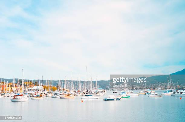 hobart, tasmania - april 02, 2012: yachts moored in hobart marina on a blue sky day. some white clouds on the sky. - launceston australia stock pictures, royalty-free photos & images