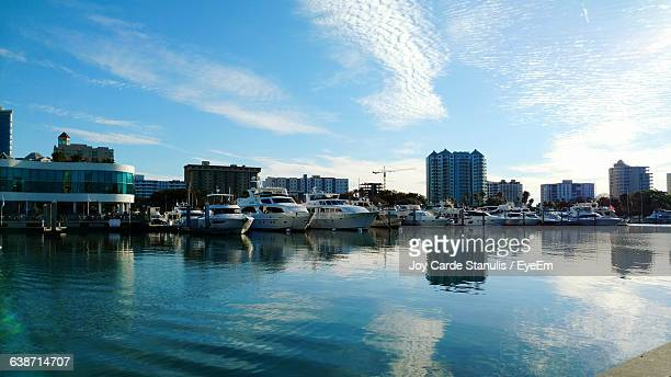 yachts moored in sea by buildings - sarasota stock photos and pictures