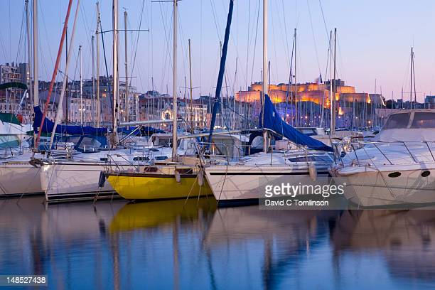Yachts moored in Vieux Port at dusk with illuminated Fort St-Nicolas in background.
