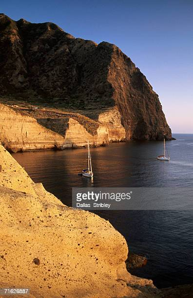 yachts moored near giant cliffs, pollara, italy - isole eolie foto e immagini stock