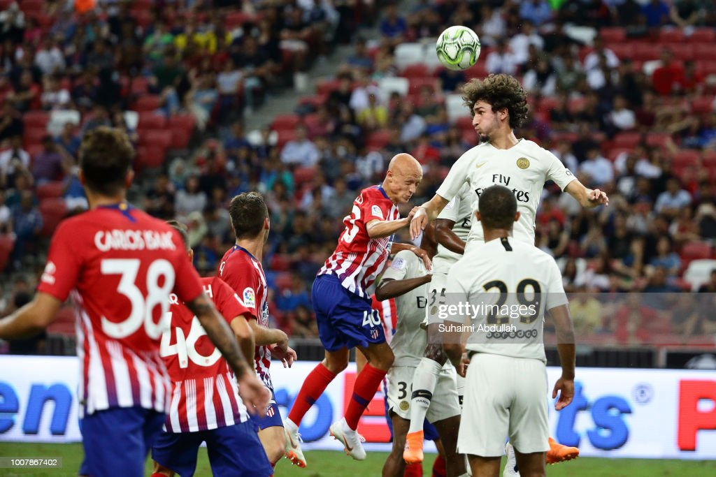 Yacine Adli of Paris Saint Germain and V'ctor Mollejo of Atletico Madrid jump for the ball during the International Champions Cup 2018 match between Atletico Madrid and Paris Saint Germain at the National Stadium on July 30, 2018 in Singapore.