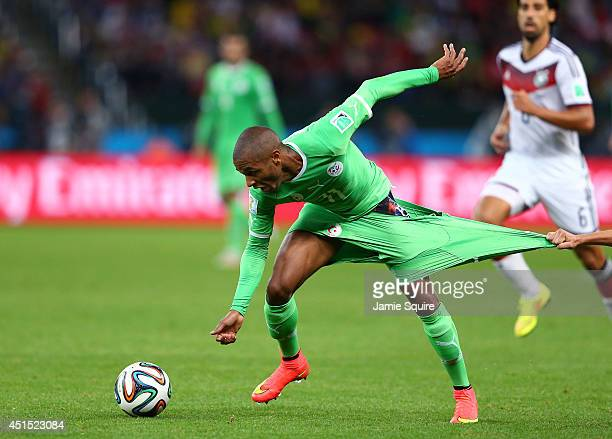 Yacine Brahimi of Algeria has his shorts pulled by Philipp Lahm of Germany during the 2014 FIFA World Cup Brazil Round of 16 match between Germany...