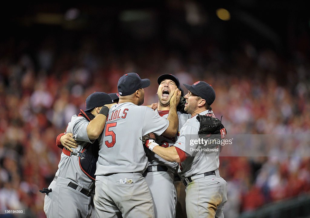 Yadier Molina, Albert Pujols #5, Chris Carpenter #29 and Nick Punto #8 of the St. Louis Cardinals celebrate after they won 1-0 againt the Philadelphia Phillies during Game Five of the National League Divisional Series at Citizens Bank Park on October 7, 2011 in Philadelphia, Pennsylvania.