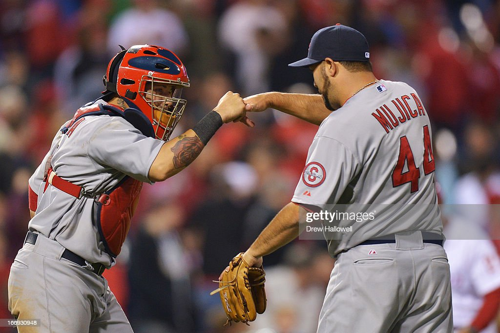 Yadier Molina #4 and Edward Mujica #44 of the St. Louis Cardinals celebrate a 4-3 win over the Philadelphia Phillies at Citizens Bank Park on April 18, 2013 in Philadelphia, Pennsylvania.