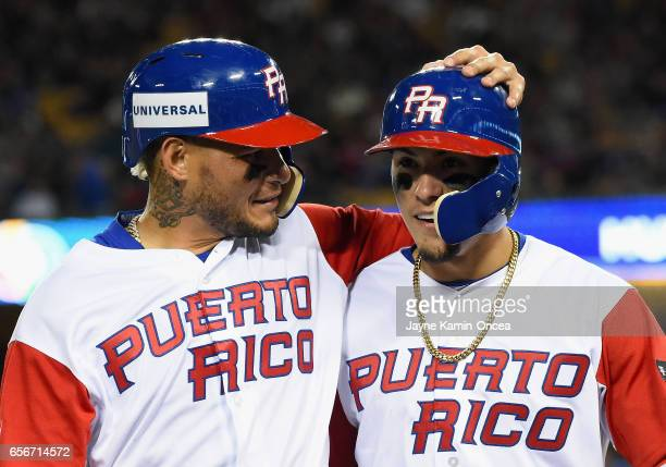 Yadier Molina and Javier Baez of team Puerto Rico walk into the dugout after both being out on a double play in the eighth inning against the United...