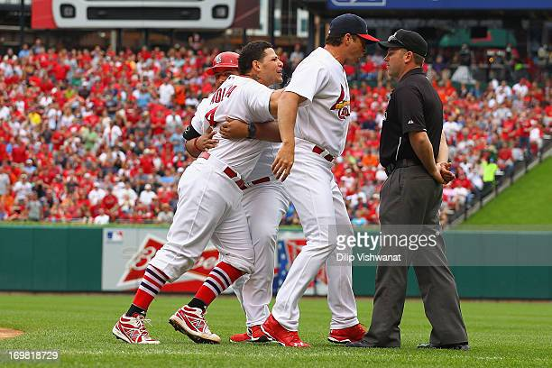 Yadier Molina and manager Mike Matheny both of the St Louis Cardinals argue with umpire Clint Fagan after Molina was ejected from the game by Fagen...