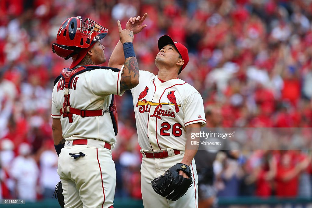Yadier Molina #4 and Seung Hwan Oh #26 of the St. Louis Cardinals celebrate after beating the Pittsburgh Pirates at Busch Stadium on October 1, 2016 in St. Louis, Missouri.