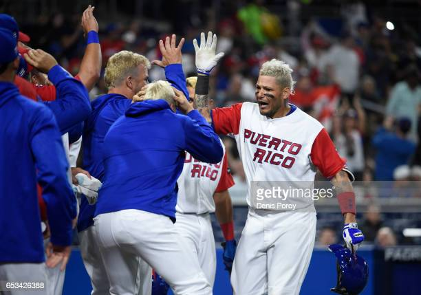 Yadier Molina of Puerto Rico right is congratulated after hitting a solo home run during the sixth inning of the World Baseball Classic Pool F Game...