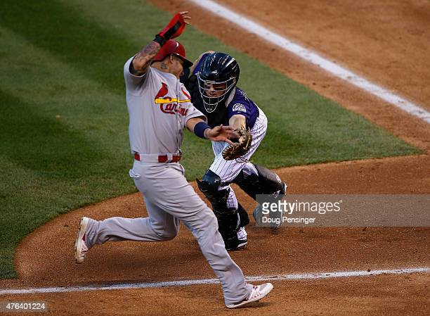 Yadier Molina of the St Louis Cardinals avoids the tag by catcher Nick Hundley of the Colorado Rockies to score on a sacrifice fly by Ed Easley of...