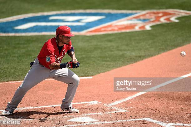 Yadier Molina of the St Louis Cardinals bunts during the second inning of a spring training game against the Atlanta Braves at Champion Stadium on...