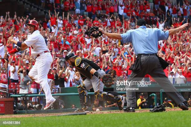 Yadier Molina of the St Louis Cardinals celebrates after scoring the gamewinning run against Russell Martin of the Pittsburgh Pirates in the ninth...