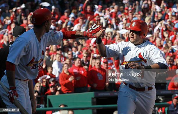 Yadier Molina of the St Louis Cardinals celebrates with Adam Wainwright after scoring on a wild pitch in the second inning against the Washington...
