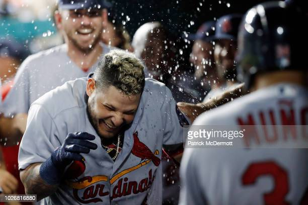 Yadier Molina of the St Louis Cardinals celebrates with his teammates in the dugout after hitting a grand slam in the ninth inning against the...