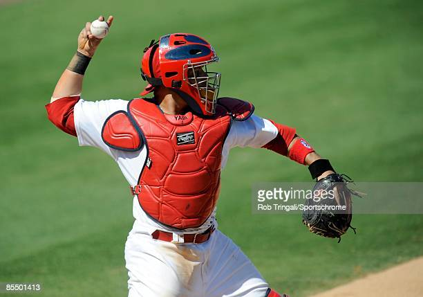 Yadier Molina of the St Louis Cardinals defends his position against the Washington Nationals during a spring training game at Roger Dean Stadium on...