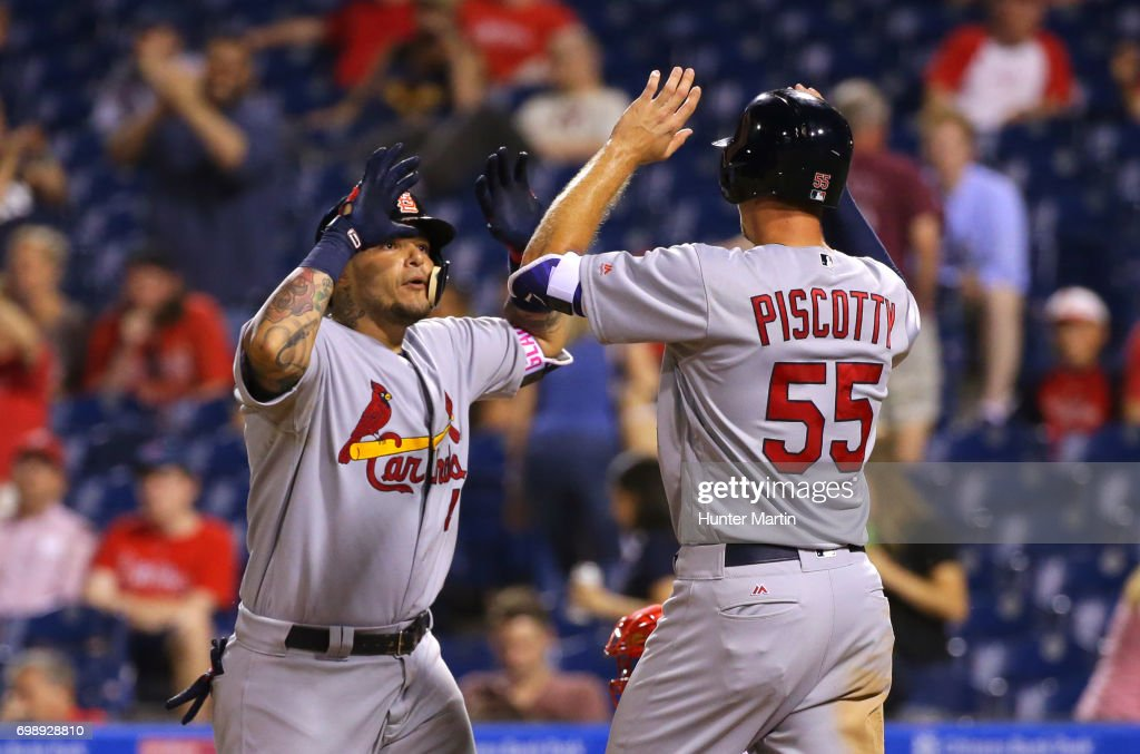 Yadier Molina #4 of the St. Louis Cardinals high fives Stephen Piscotty #55 at home plate after hitting a two-run home run in the 11th inning during a game against the Philadelphia Phillies at Citizens Bank Park on June 20, 2017 in Philadelphia, Pennsylvania. The Cardinals won 8-1 in 11 innings.