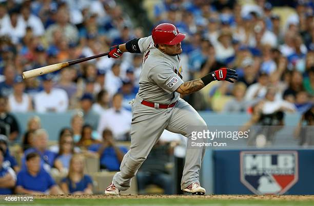 Yadier Molina of the St Louis Cardinals hits a single to load the bases in the seventh inning against the Los Angeles Dodgers during Game One of the...