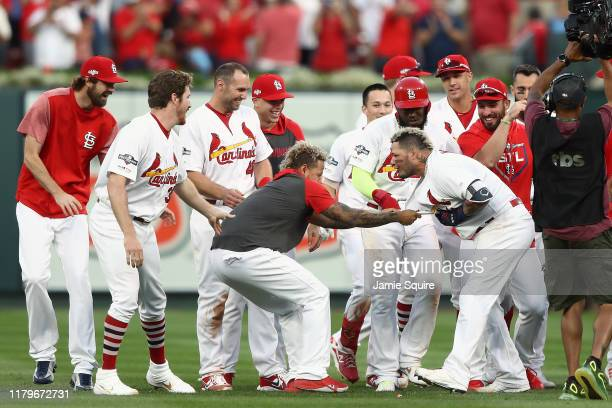 Yadier Molina of the St. Louis Cardinals is congratulated by his teammates after he hits a walk-off sacrifice fly to give his team the 5-4 win over...