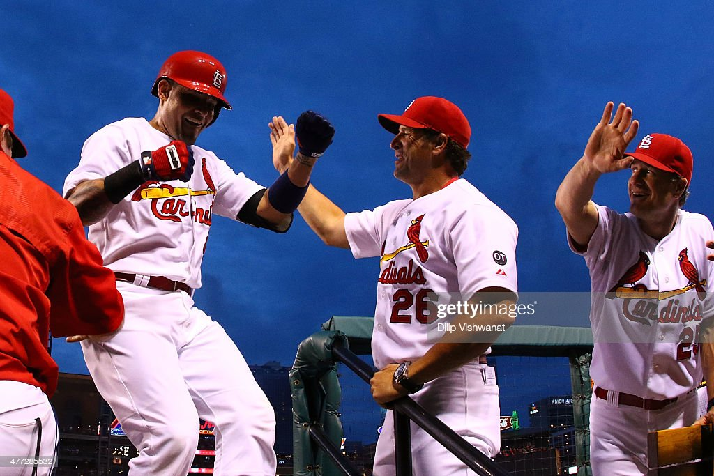 Yadier Molina #4 of the St. Louis Cardinals is congratulated by manager Mike Matheny #26 and coach David Bell #25 of the St. Louis Cardinals after hitting a solo home run against the Minnesota Twins in the fourth inning at Busch Stadium on June 15, 2015 in St. Louis, Missouri.