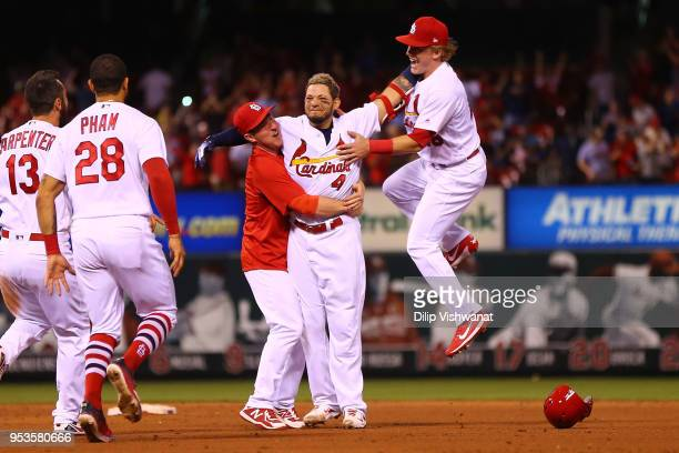 Yadier Molina of the St Louis Cardinals is mobbed by Jedd Gyorko and Harrison Bader of the St Louis Cardinals after hitting a walkoff single against...