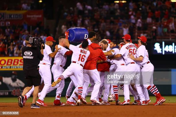 Yadier Molina of the St Louis Cardinals is mobbed by teammates after hitting a walkoff single against the Chicago White Sox in the ninth inning at...