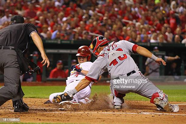 Yadier Molina of the St Louis Cardinals is tagged out at home by Wilson Ramos of the Washington Nationals in the fourth inning at Busch Stadium on...