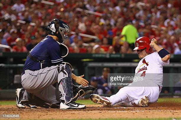 Yadier Molina of the St Louis Cardinals is tagged out at home plate by Nick Hundley of the San Diego Padres in the sixth inning at Busch Stadium on...