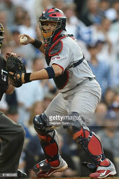 Yadier Molina of the St Louis Cardinals looks to throw the ball to first base in Game Two of the NLDS during the 2009 MLB Playoffs against the Los...