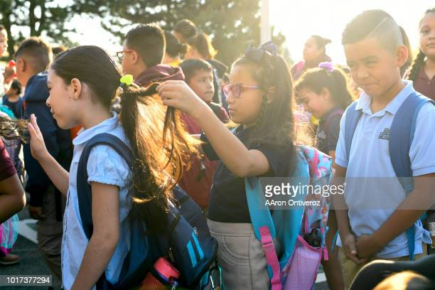 Yadira Rodriguez gets her hair done by Mareli PadillaMejia on the first day of school at McGlone Academy on Wednesday August 15 2018