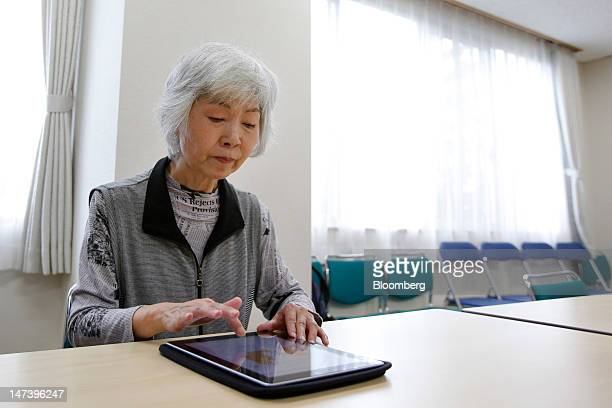 Yaemi Ike uses an Apple Inc iPad to arrange work schedules during a demonstration at Kohitsujien Care Home in Kashiwa City Chiba Prefecture Japan on...